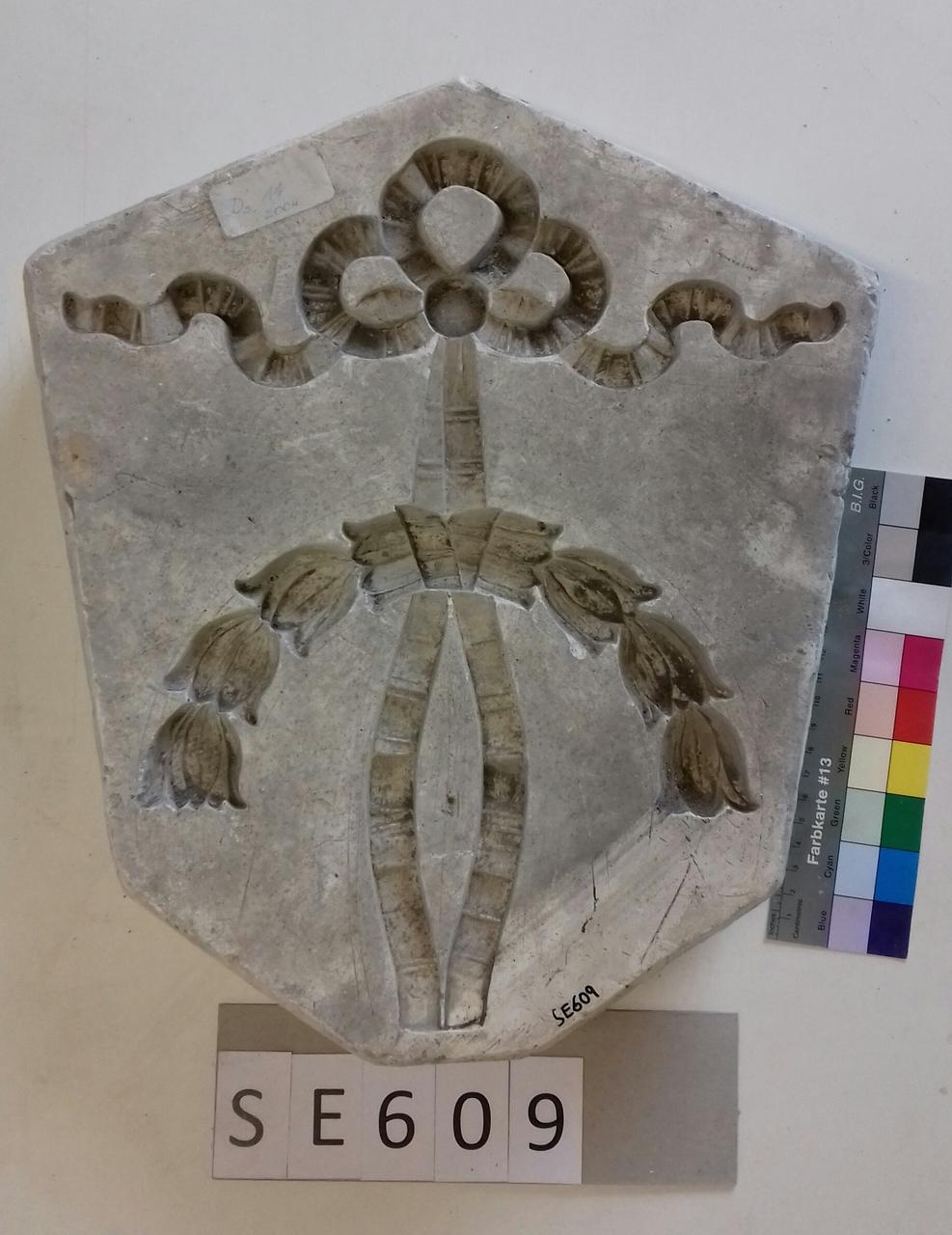 Negativform Detail floraler Halbkranz und Masche
